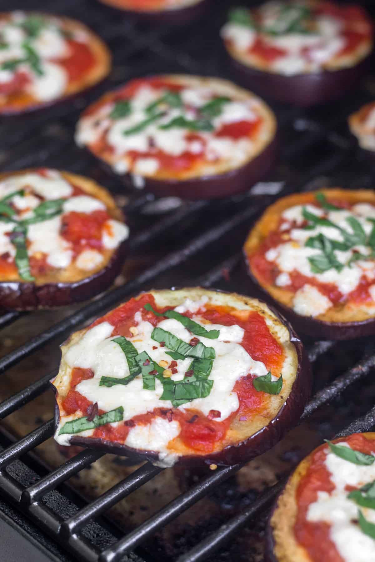 Grilled Eggplant Pizza topped with fresh basil and red pepper flakes on the grill
