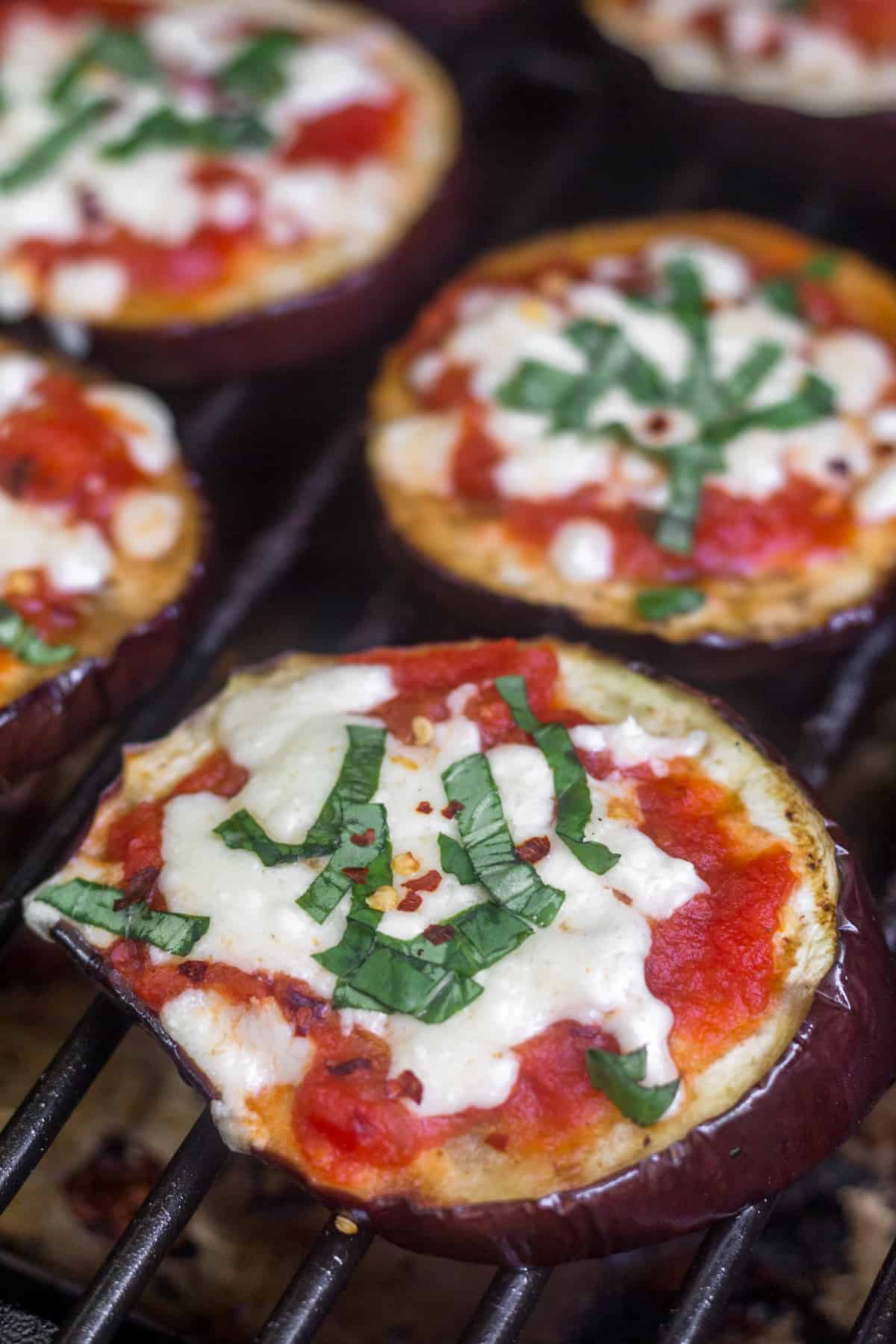Close up on a grilled eggplant pizza sitting on a grill with other eggplant pizzas behind it