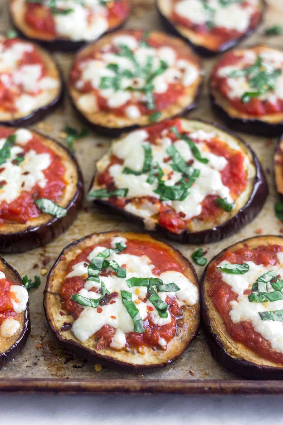 A bunch of Grilled Eggplant Pizza sprinkled with basil and red pepper flakes on a baking sheet