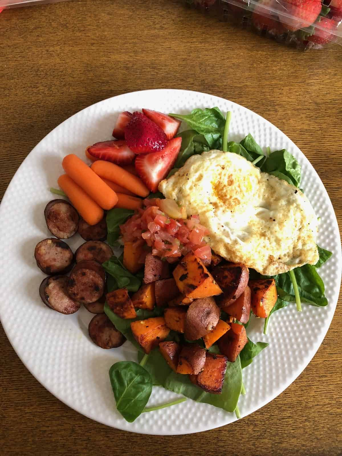 Breakfast plate of greens, fried egg, sweet potato, chicken sausage, carrots, strawberries, and salsa