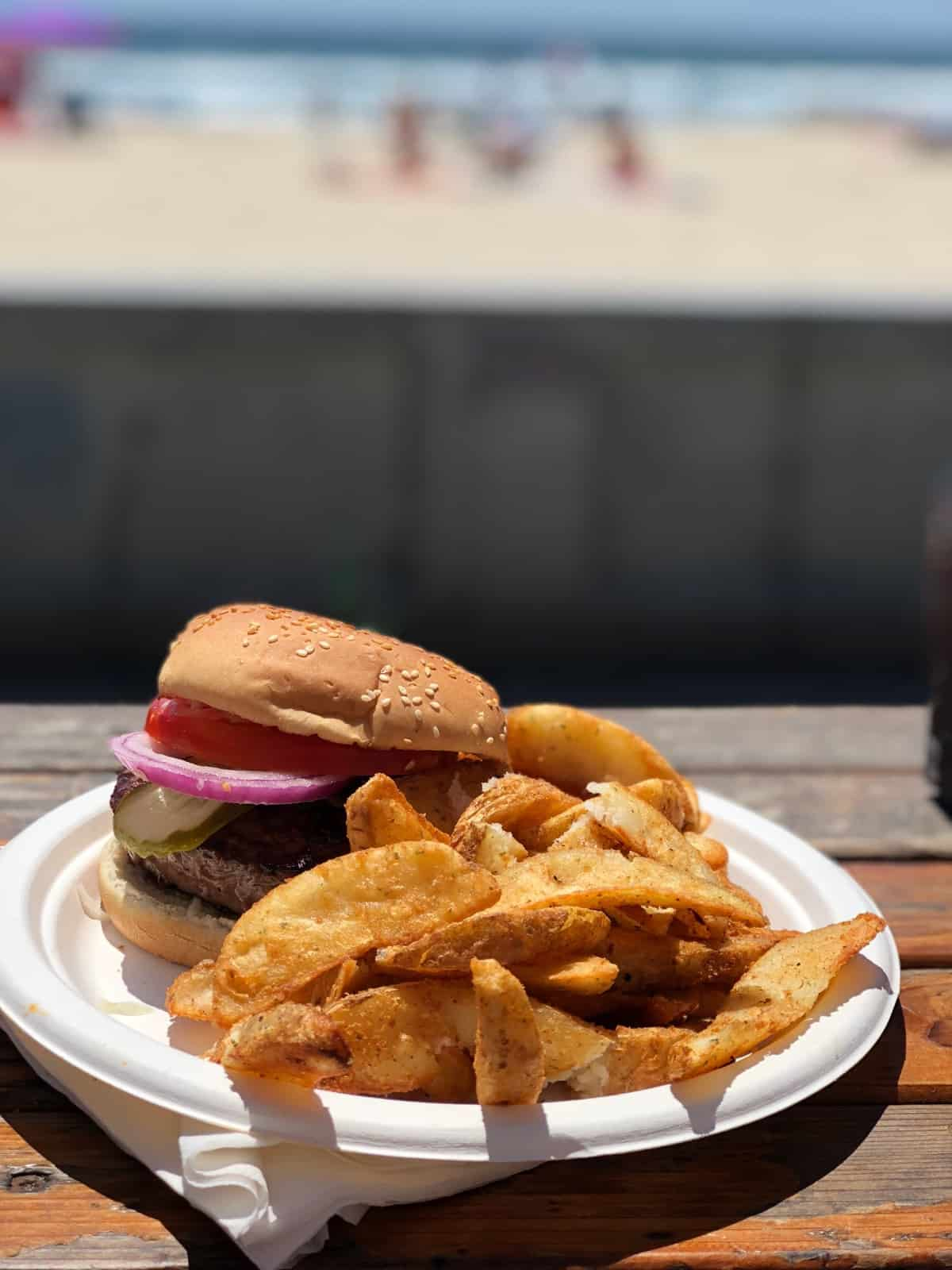 Burger and fries from Woody's on the strand with the beach in the background in San Diego
