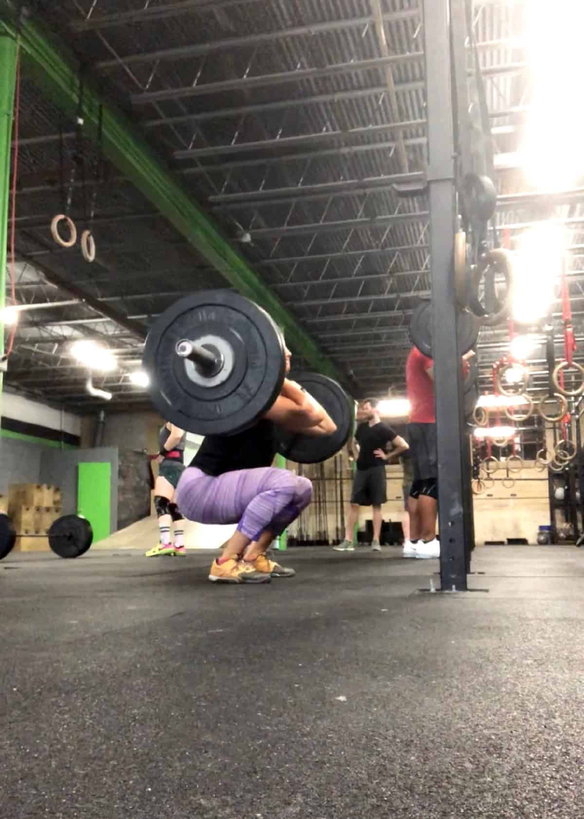 Girl in the bottom of a squat doing front squats with a loaded barbell