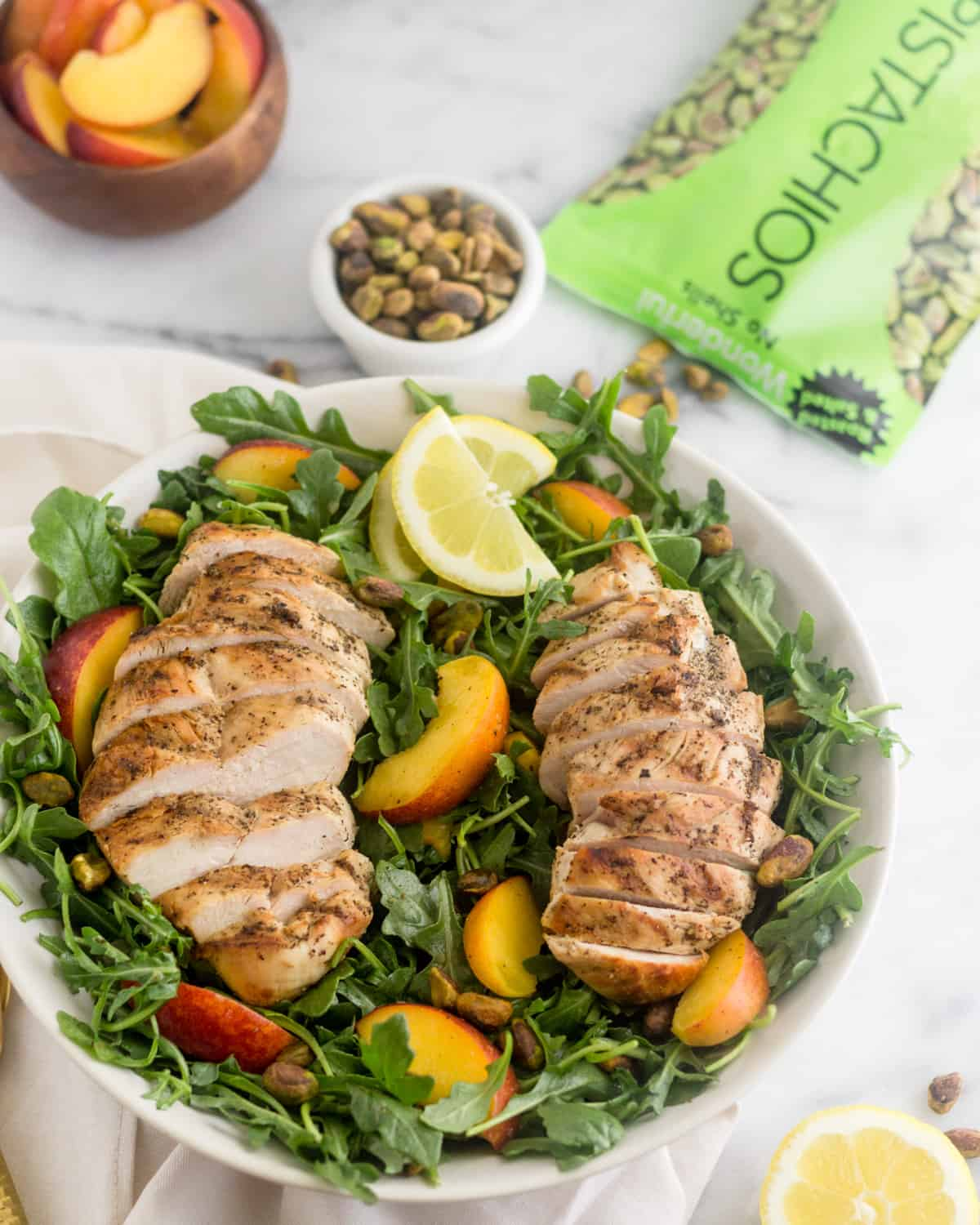 Peach and Pistachio Salad with Grilled Chicken salad in a large bowl with a bag of pistachios, a bowl of pistachios, and a bowl of cut up peaches behind it