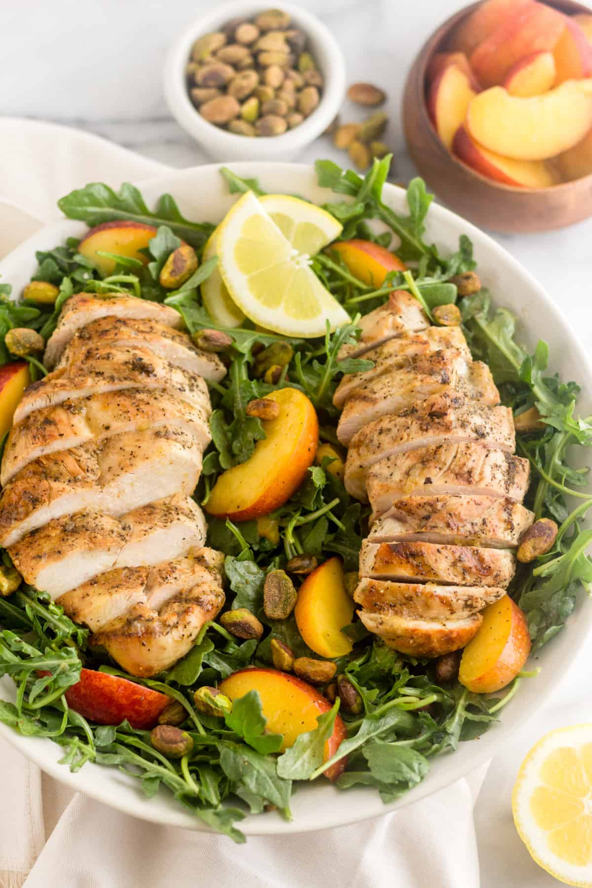 Large Peach and Pistachio Salad with Grilled Chicken garnished with lemon wedges