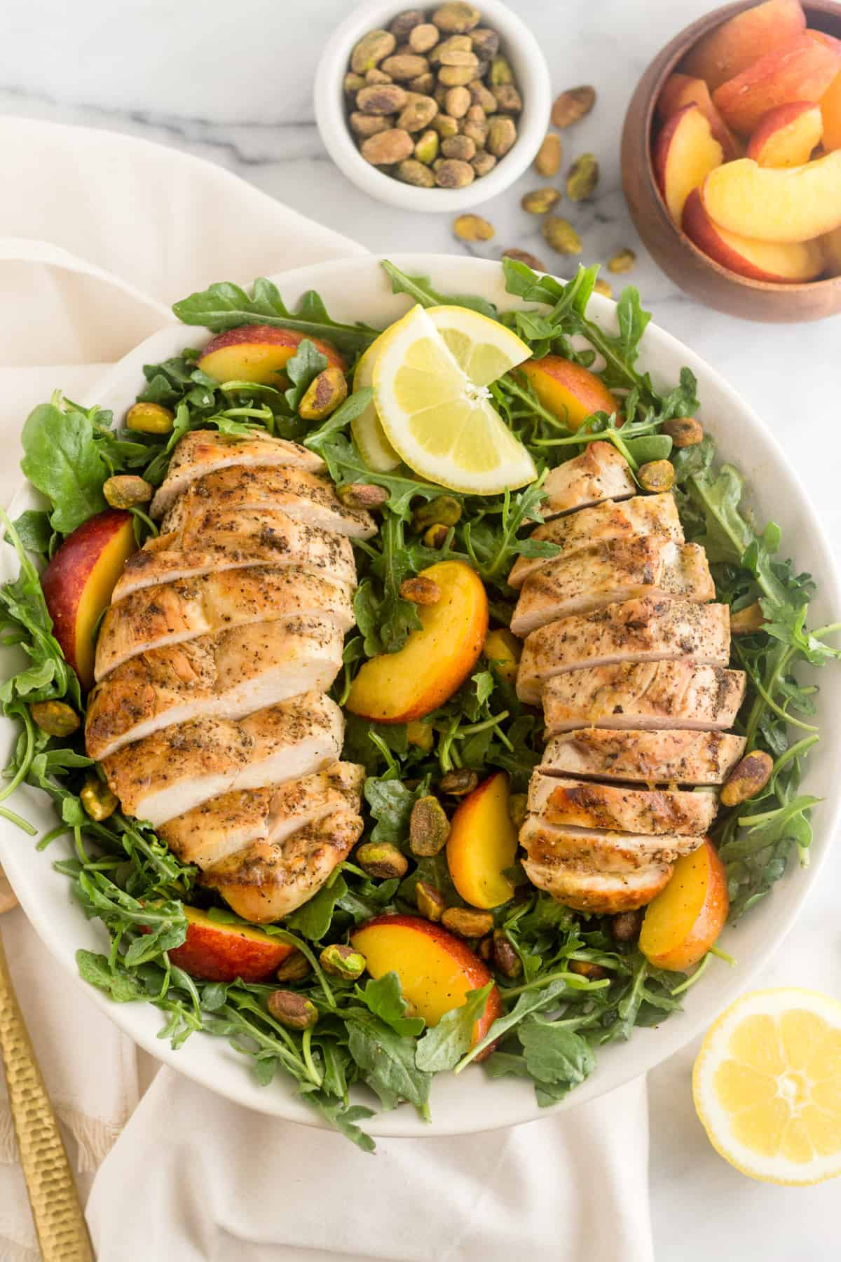 Peach and Pistachio Salad with Grilled Chicken in a large bowl overtop a white linen with pistachios, peaches, and half a lemon around it