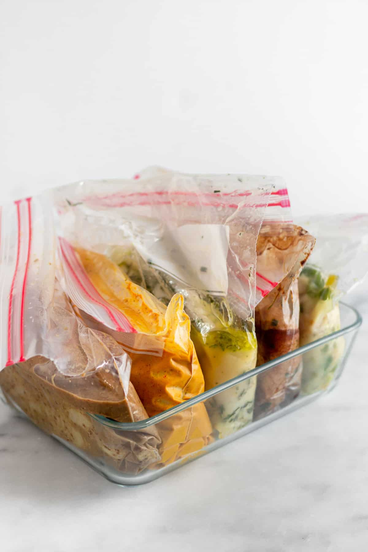 Glass baking dish with 5 bags of whole30 chicken marinade and chicken in each one