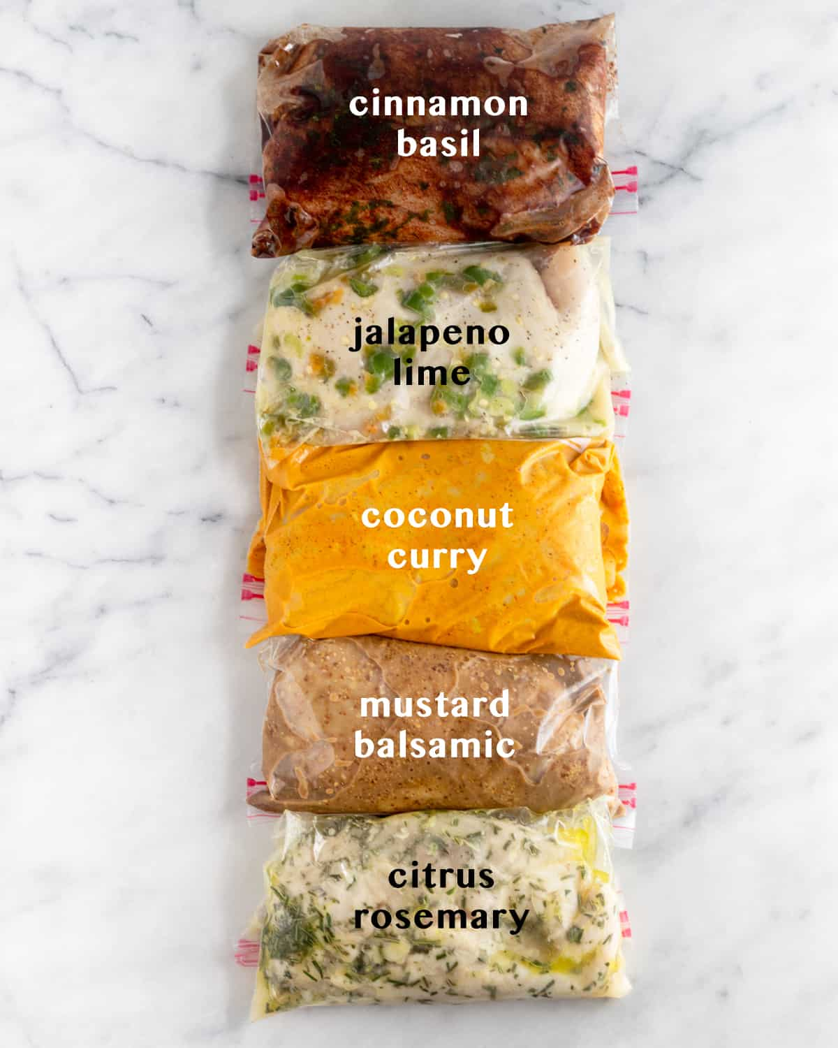 5 plastic bags on white counter top filled with Whole30 Chicken Marinade 5 different ways. Text overlay of what each marinade is - cinnamon basil, jalapeño lime, coconut curry, mustard balsamic, citrus rosemary.