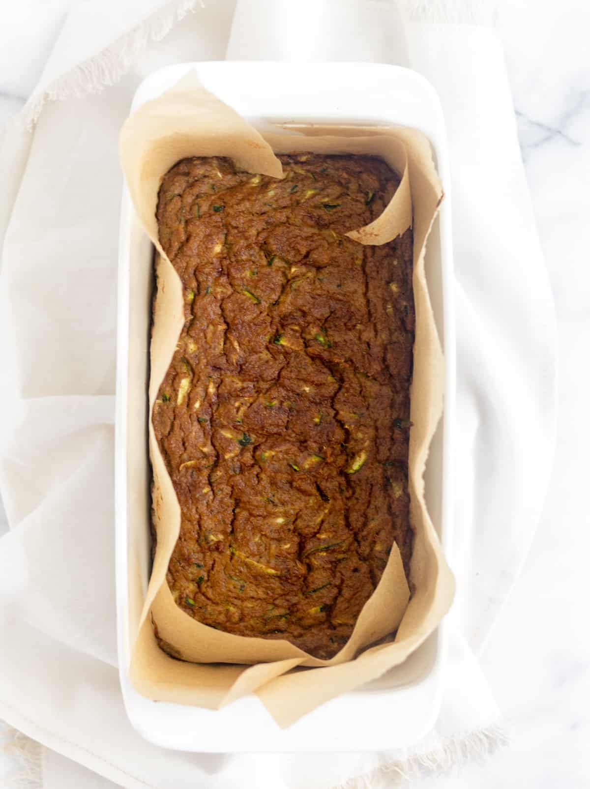 Paleo Zucchini Banana Bread in a glass loaf pan with parchment paper around it on a white marble countertop
