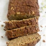 Three slices of Paleo Zucchini Banana Bread cut off from the loaf falling over with the loaf and a banana behind it