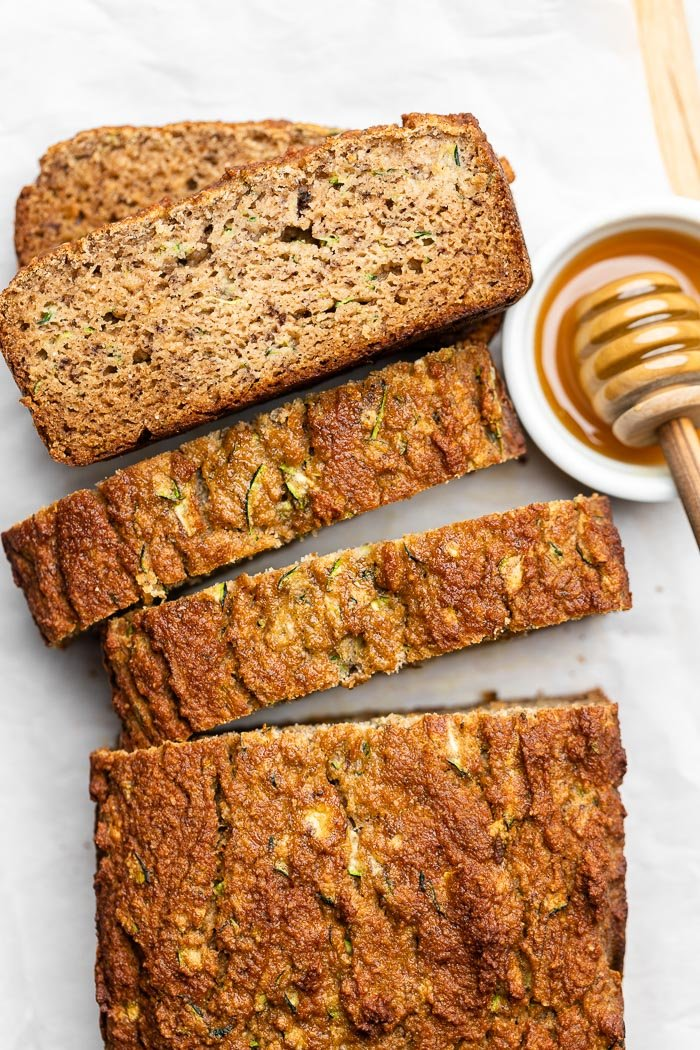 Overhead shot of sliced zucchini banana bread with the pieces spread out and some slices stacked on top of each other. Next to is a bowl of honey with a honey dipper.