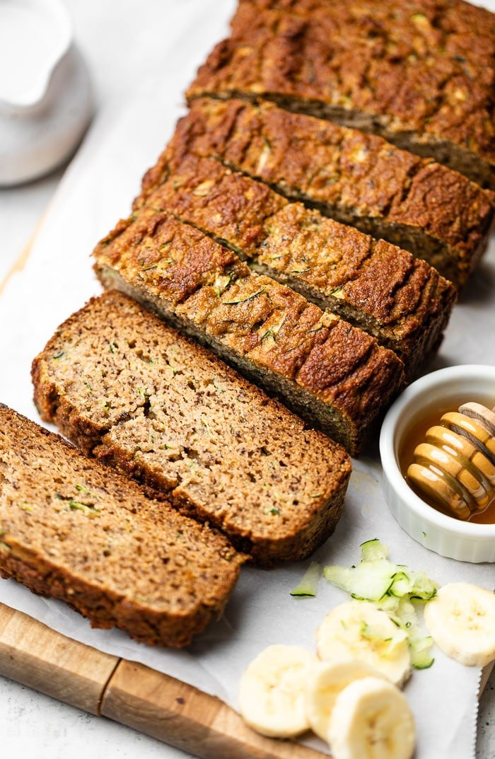 Healthy zucchini banana bread sliced on cutting board. Next to it is some shredded zucchini, sliced banana, and a bowl of honey.