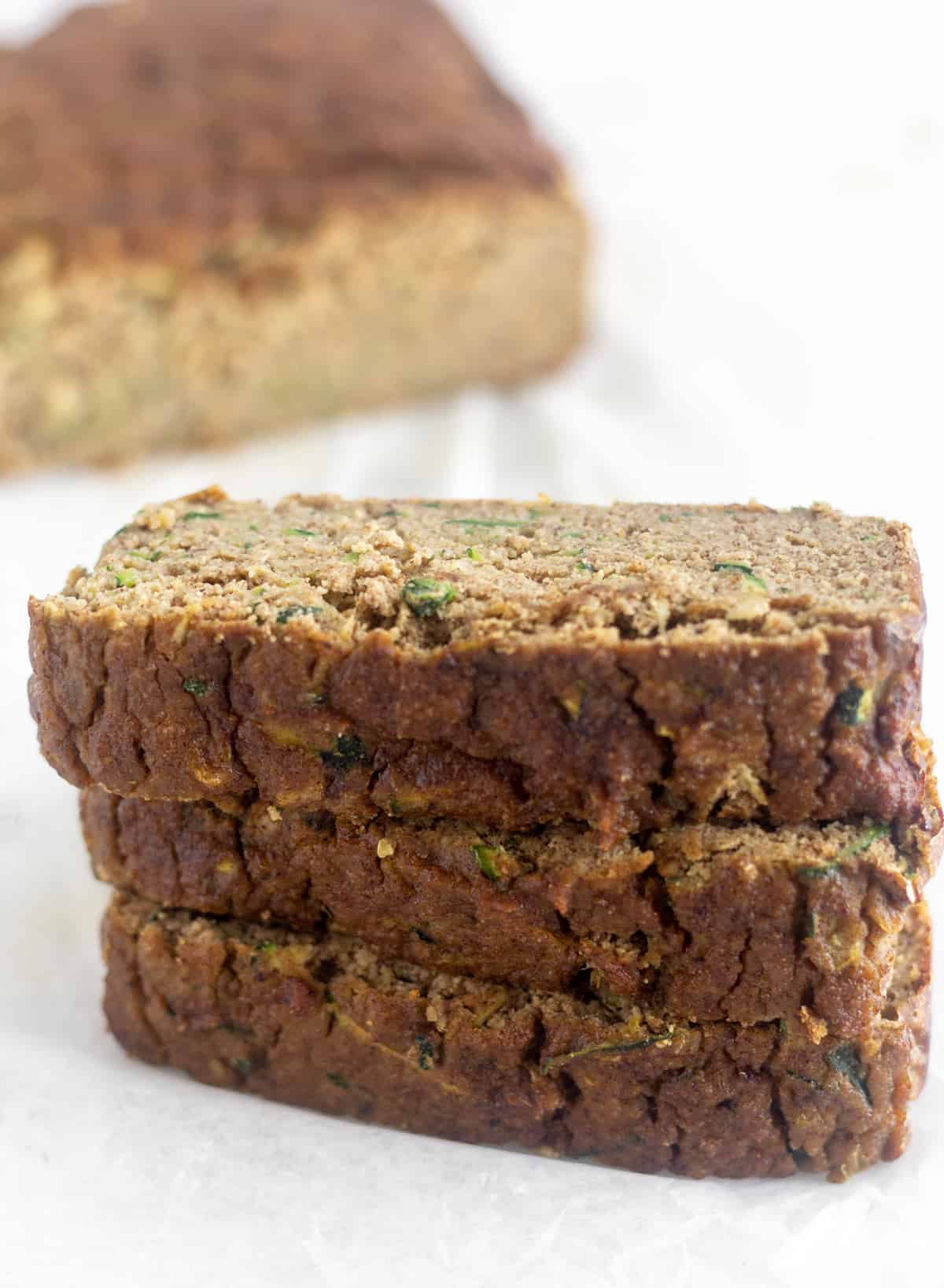 Three pieces of Zucchini Banana Bread stacked on top of each other with the rest of the load behind it