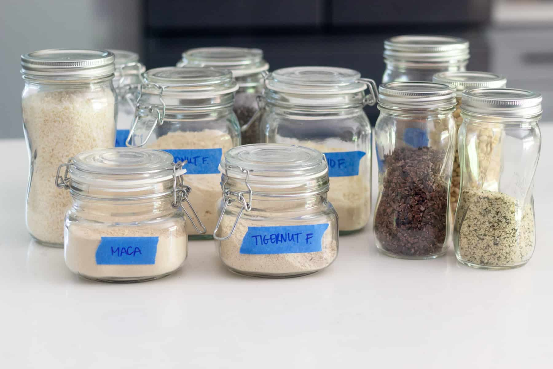 A bunch of glass jars with different flours and pantry staples in them
