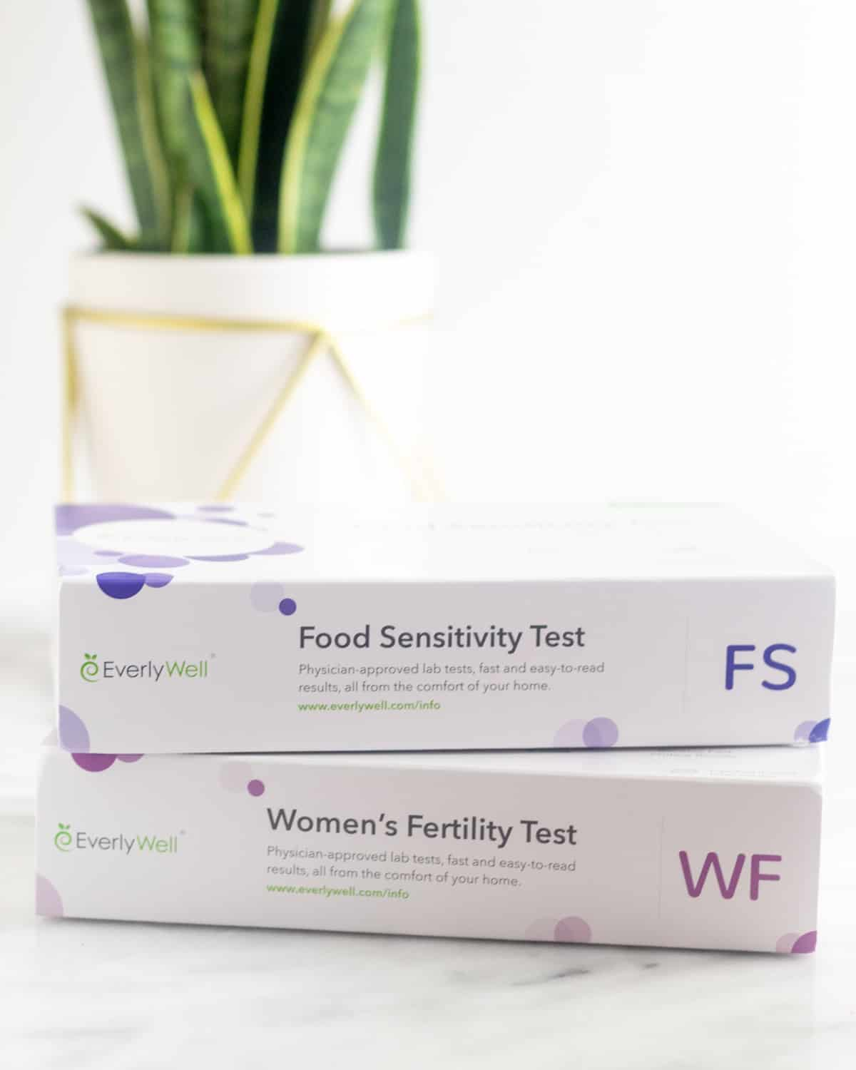 Two boxes of EverlyWell tests - one food sensitivity test and one women's fertility test - on a white counter with a plant behind it