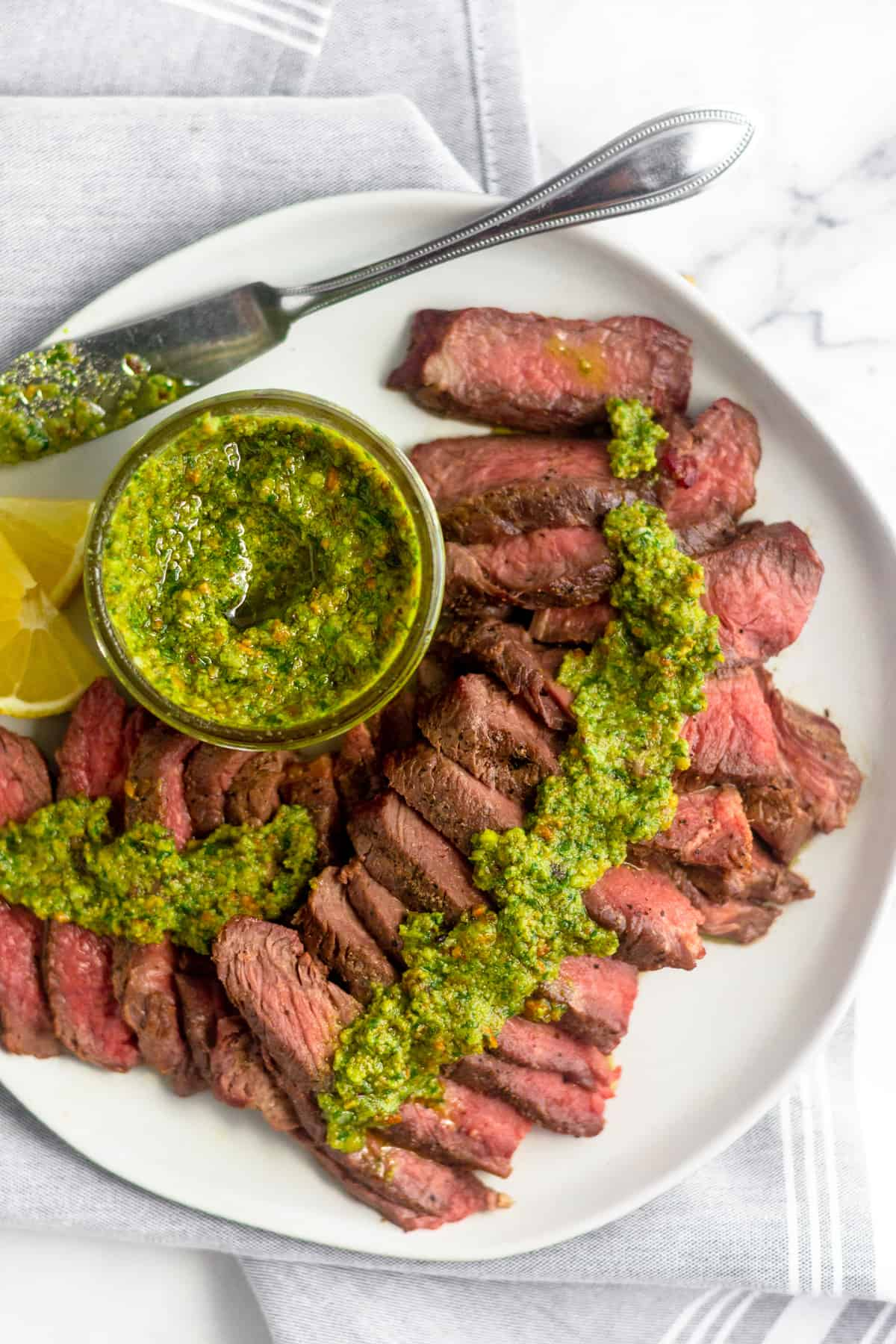 White plate with cut up grilled steak with pistachio pesto on top of it along with a jar of pistachio pesto and sliced lemon