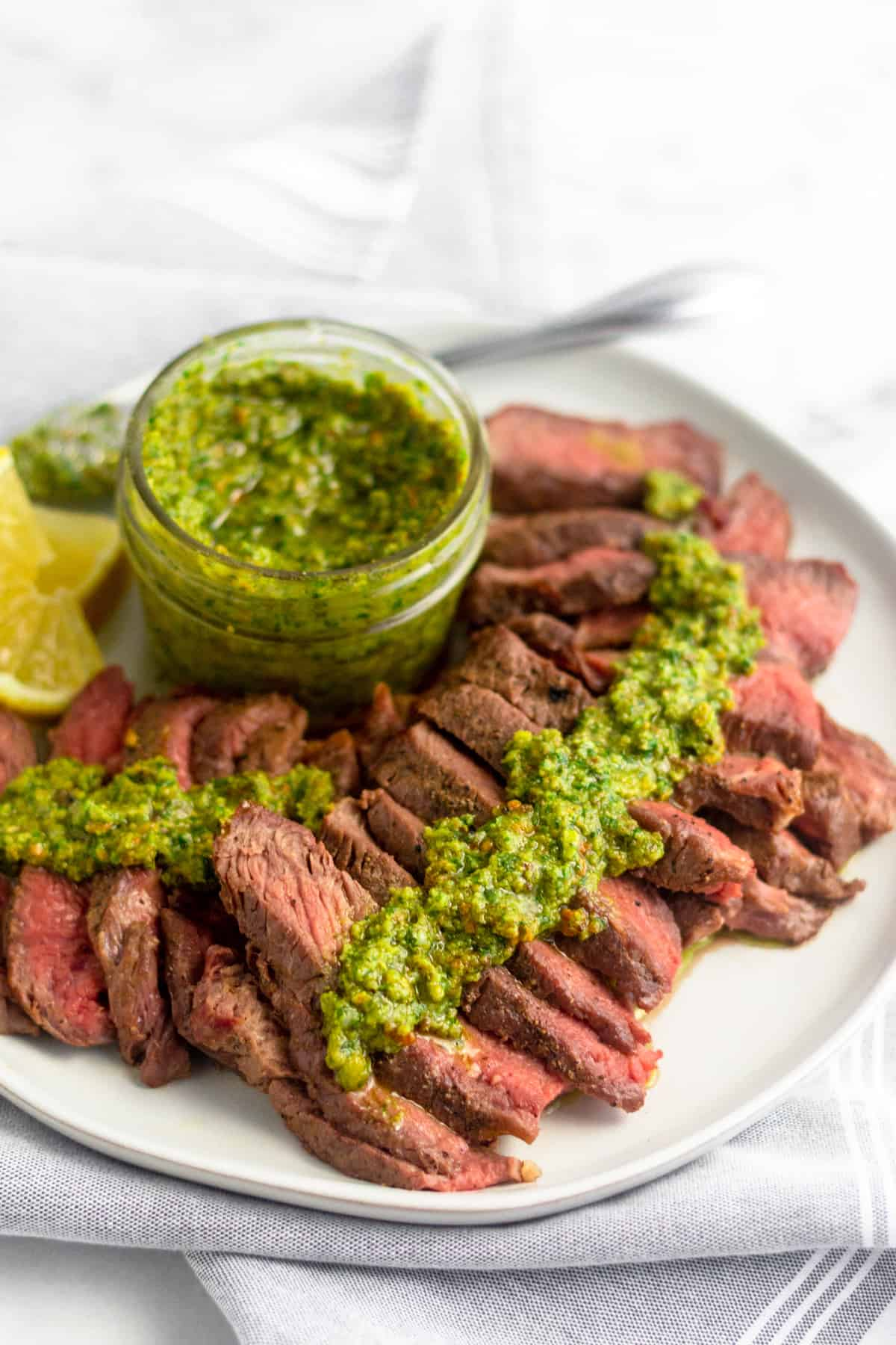 Cut up grilled steak with pistachio pesto on it on a white plate