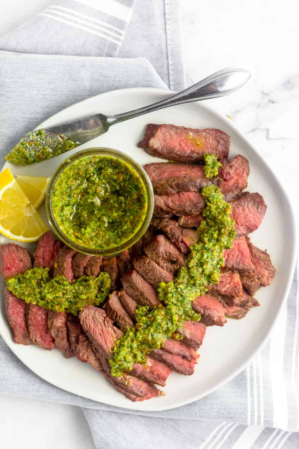 Overhead view of cut up grilled steak topped with pistachio pesto along with a jar of pesto, a small knife, and cut up lemons