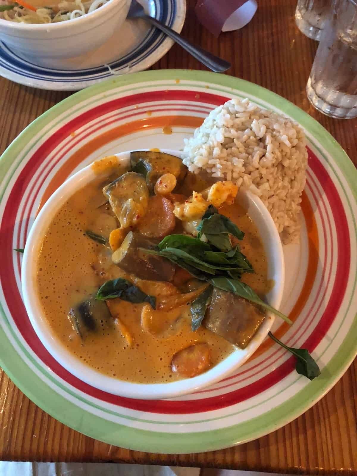 Red curry with vegetables and rice on the side