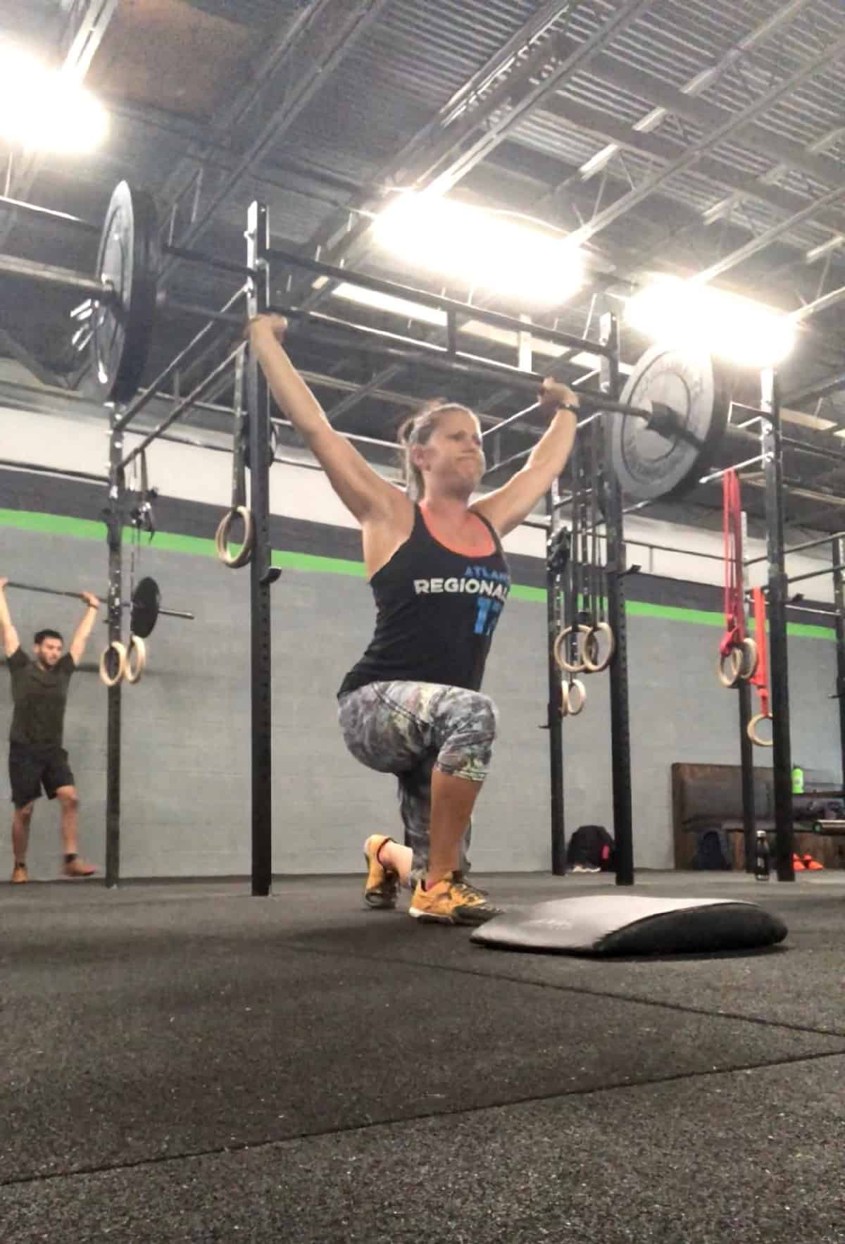Girl in a CrossFit gym doing an weighted overhead lunge with a barbell