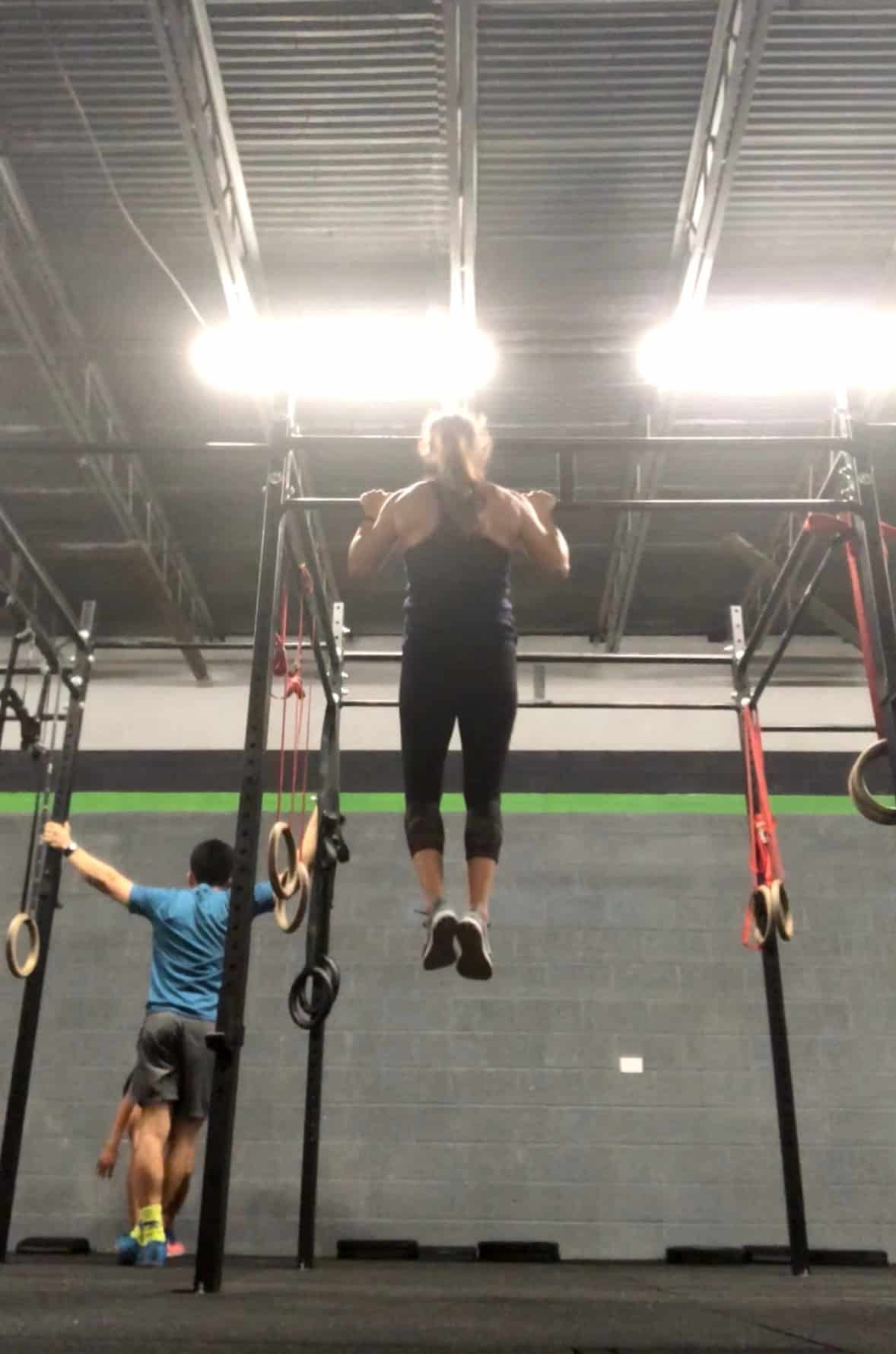 Girl doing a strict pull-up from a pull-up rig in a CrossFit gym