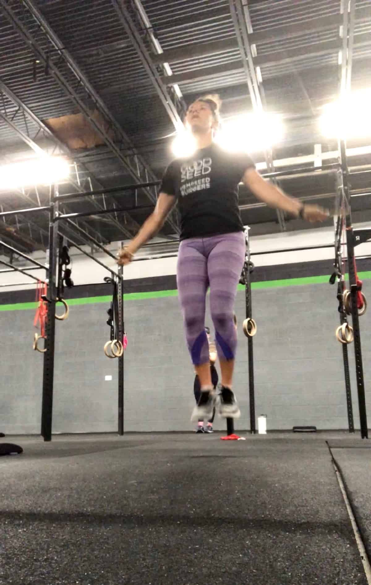 Girl in purple leggings and a tee shirt jumping rope in a CrossFit gym