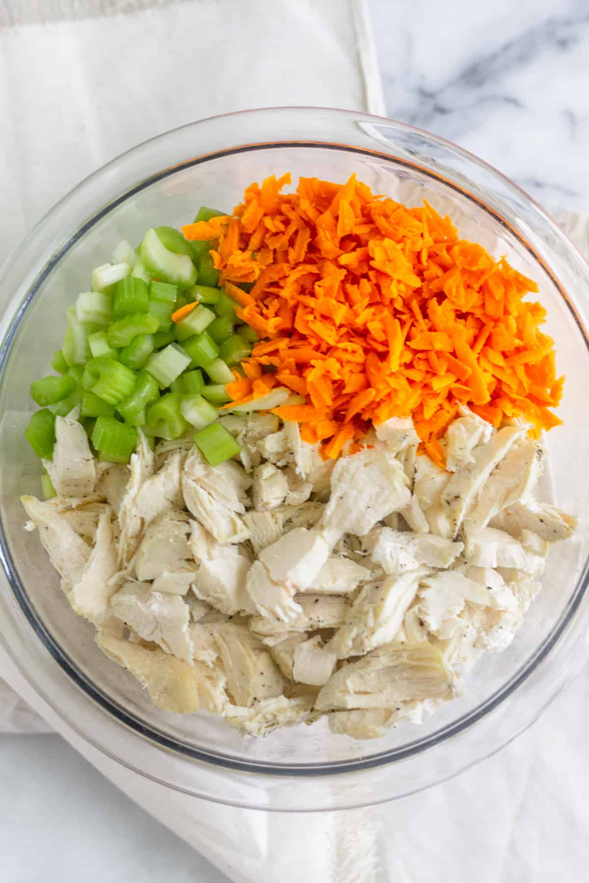 Glass bowl filled with diced chicken, shredded carrots, and diced celery on a white marble board