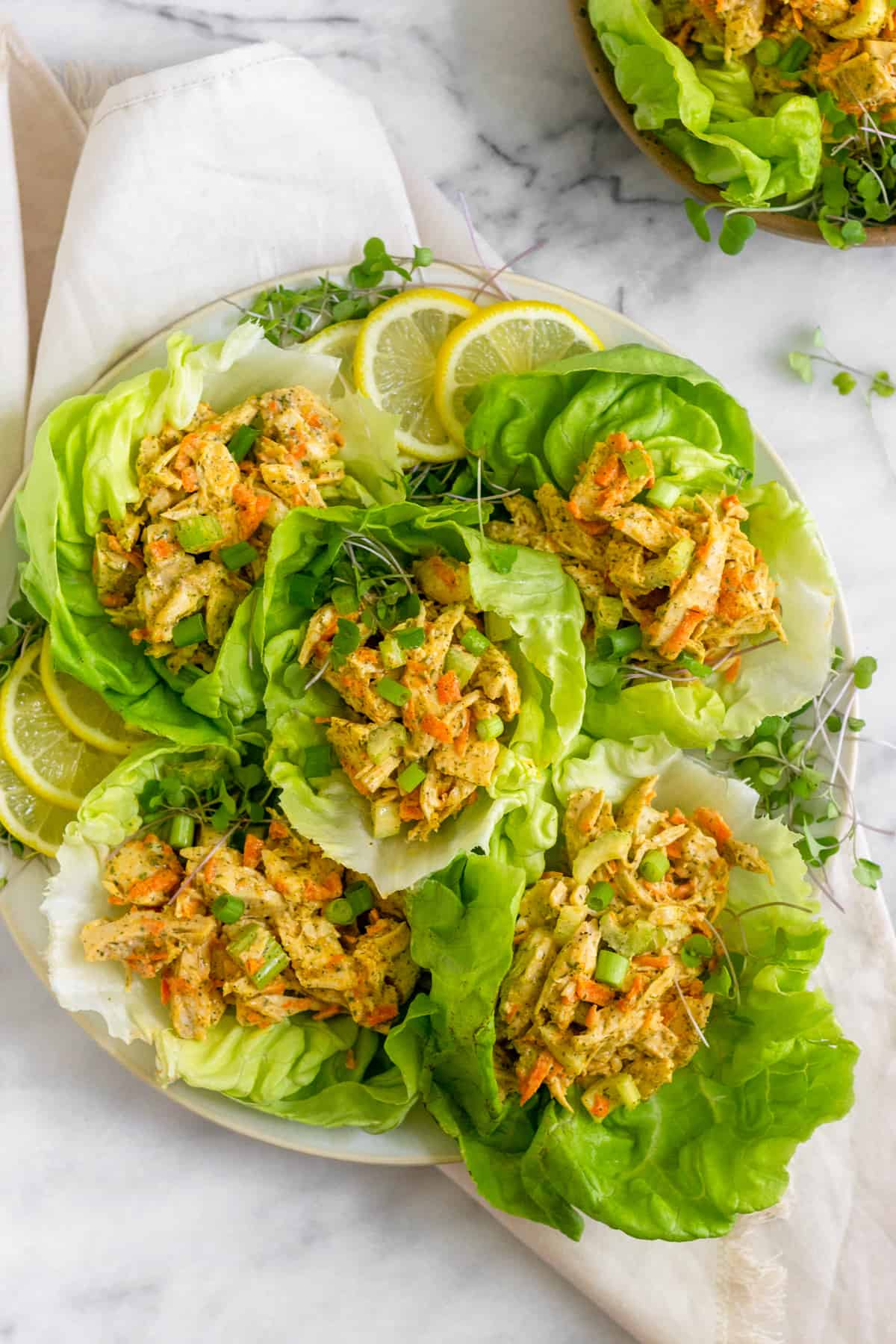 Large large over a tan linen filled with lettuce cups filled with Paleo Buffalo Ranch Chicken Salad with green onion and lemon wedges as garnish and next to a bowl of buffalo ranch chicken salad