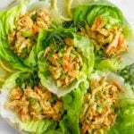 Large large filled with lettuce cups filled with Paleo Buffalo Ranch Chicken Salad with green onion and lemon wedges as garnish