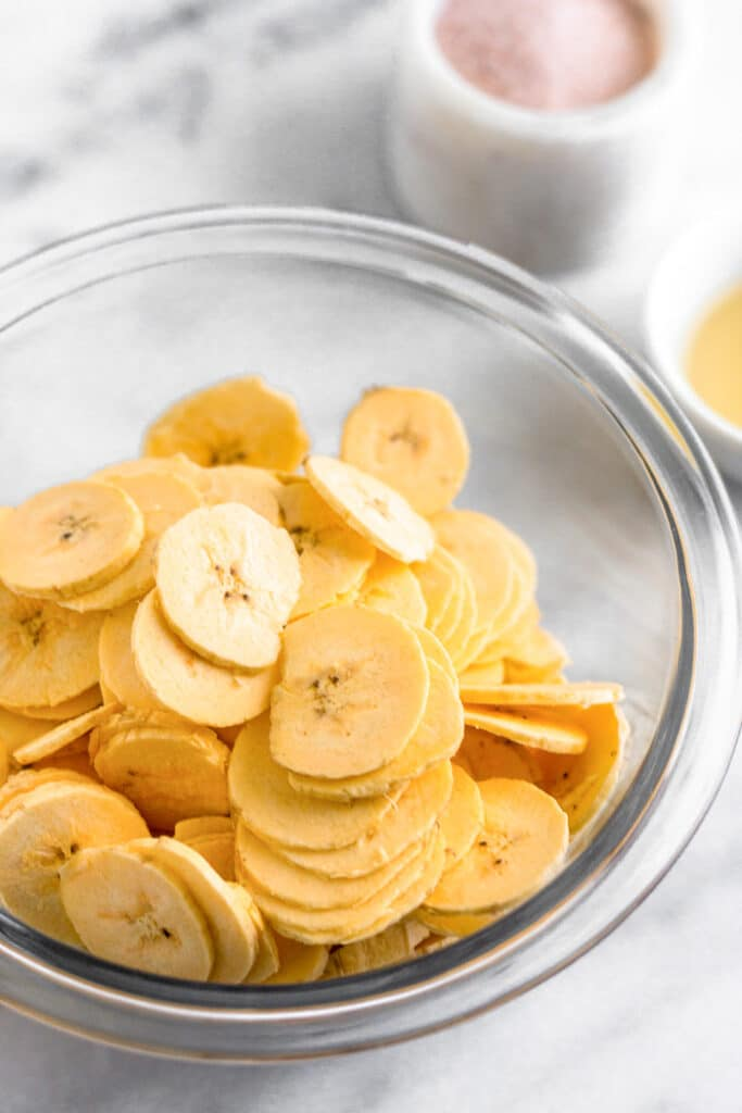 Sliced plantains in a large bowl. Behind them are a small bowl of oil and a small container of salt.