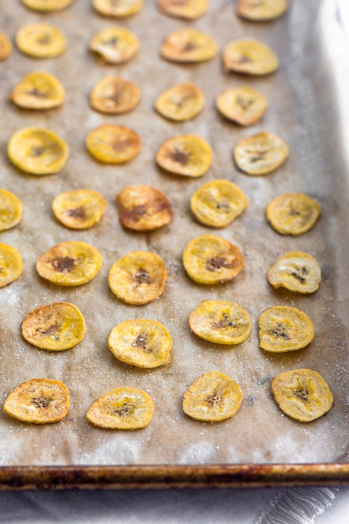 Baked plantain chips spread out on a baking sheet.