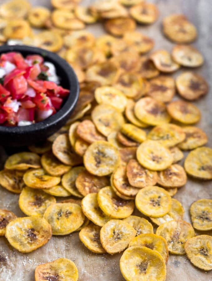 A large baking sheet with homemade baked plantain chips spread out all over with a small dish of salsa.