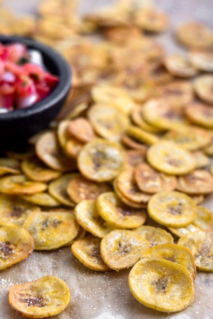Homemade plantain chips spread out on a baking sheet with a bowl of salsa next to them.