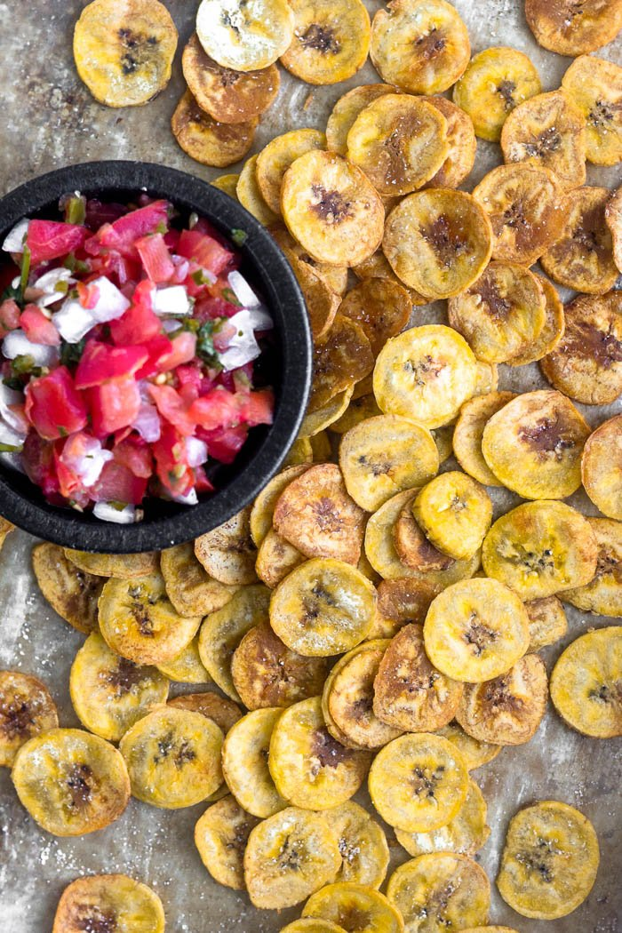 Overhead shot of baked plantain chips spread out on a baking sheet with a small dish of salsa.