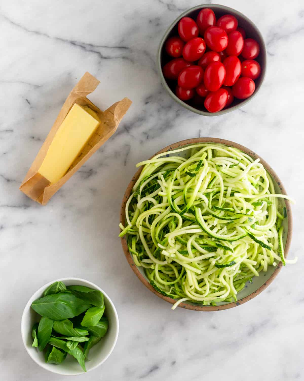 Bowl of cherry tomatoes, bowl of zucchini noodles, bowl of fresh basil, and a stick of butter on a white counter top