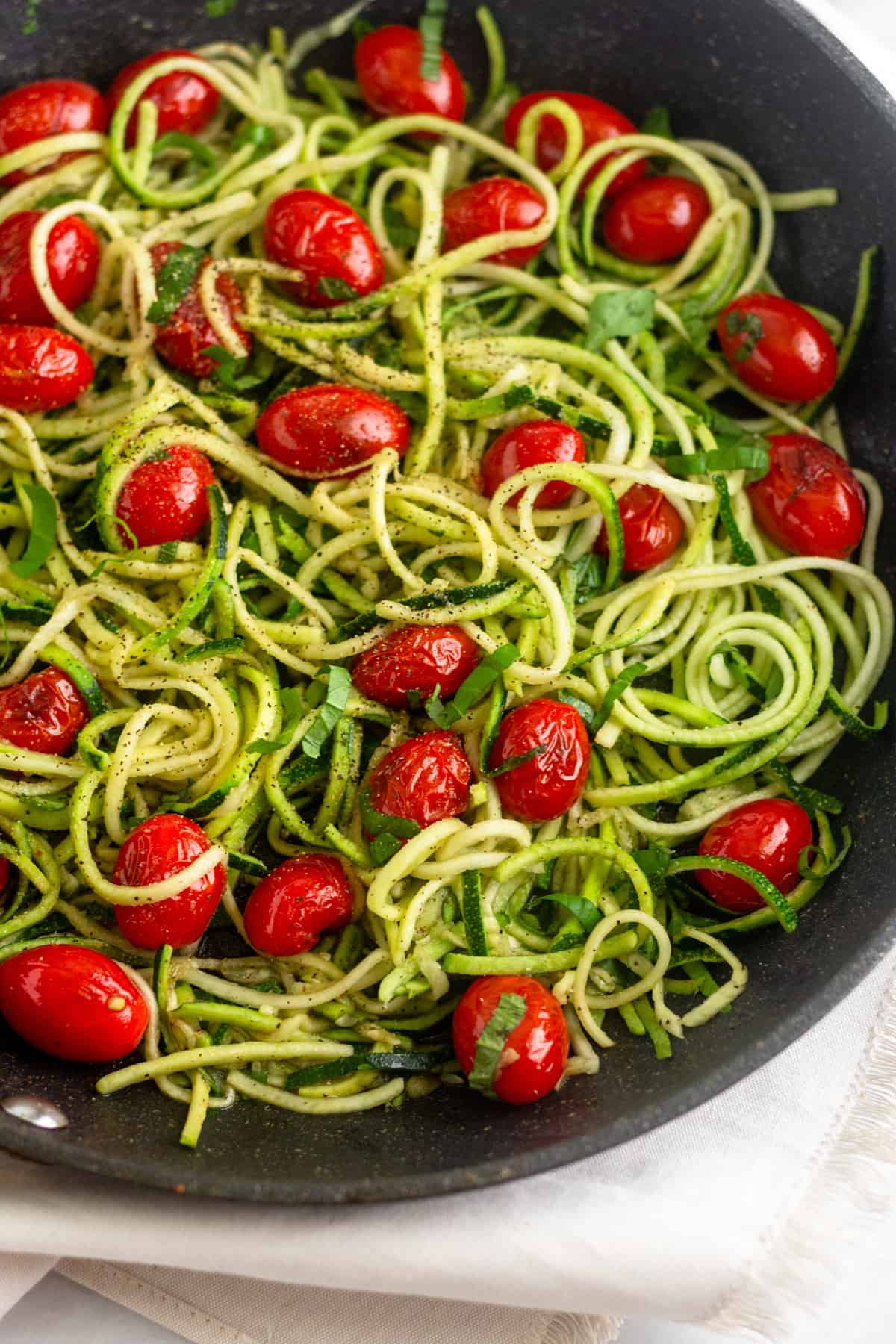 Large saute pan filled with zucchini noodles, blistered tomatoes, and fresh basil