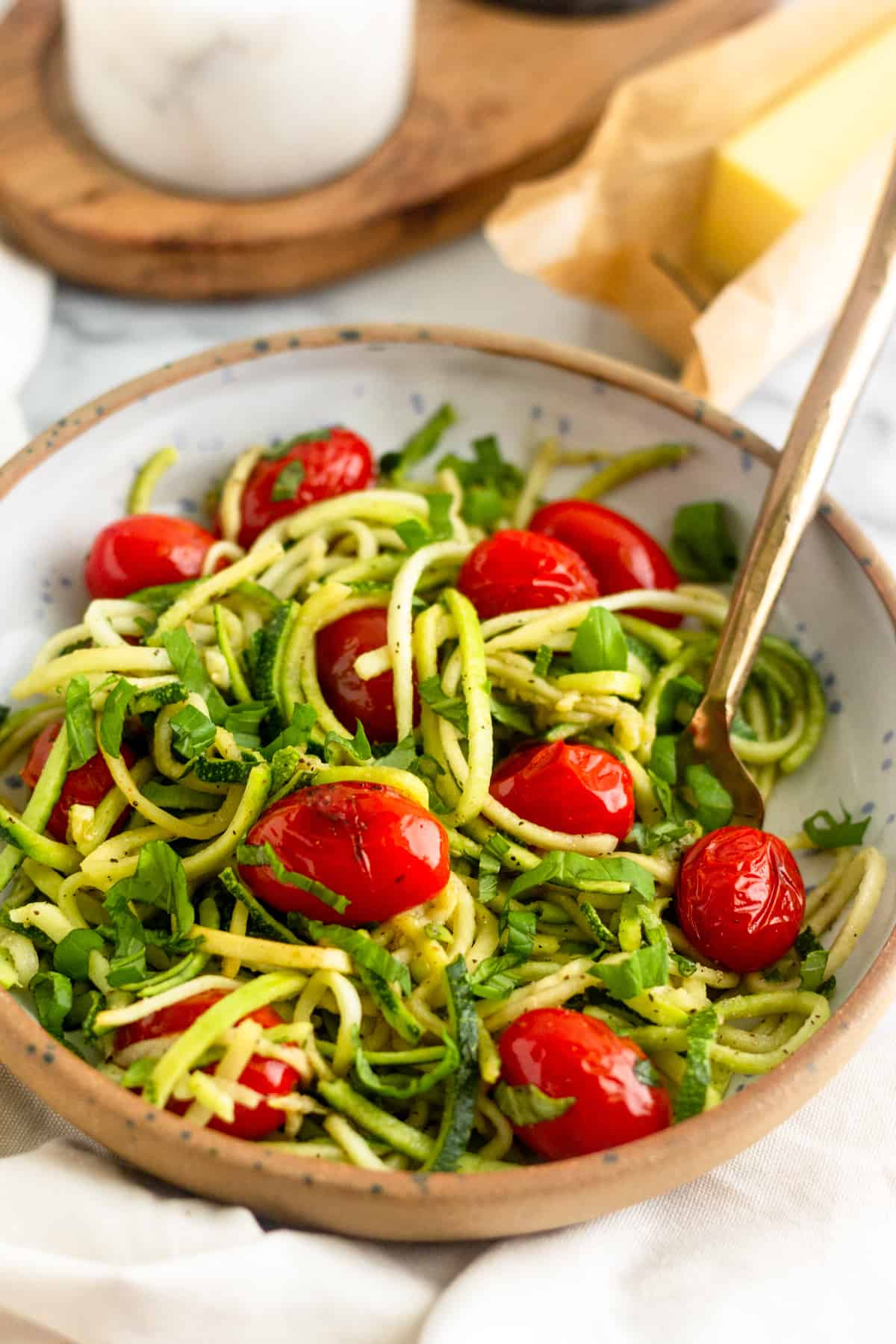 Bowl of zucchini noodles with blistered tomatoes and basil with a gold fork in it in front of a stick of butter and a salt holder
