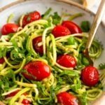 Bowl of zucchini noodles with blistered tomatoes and basil with a fork in it and a stick of butter behind it