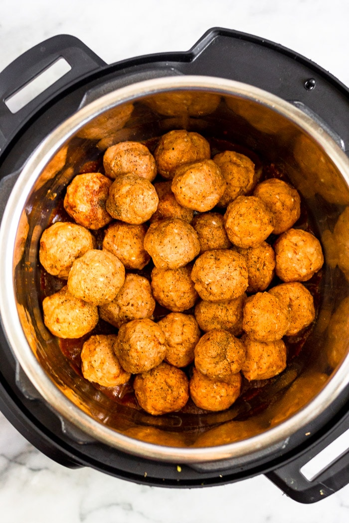 Instant pot filled with raw chicken meatballs piled on top of each other.