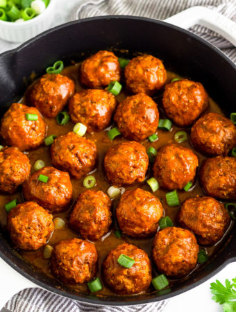 A large cast iron skillet filled with BBQ chicken meatballs covered in BBQ sauce and topped with green onions. Around it is some fresh parsley and a bowl of chopped green onions.