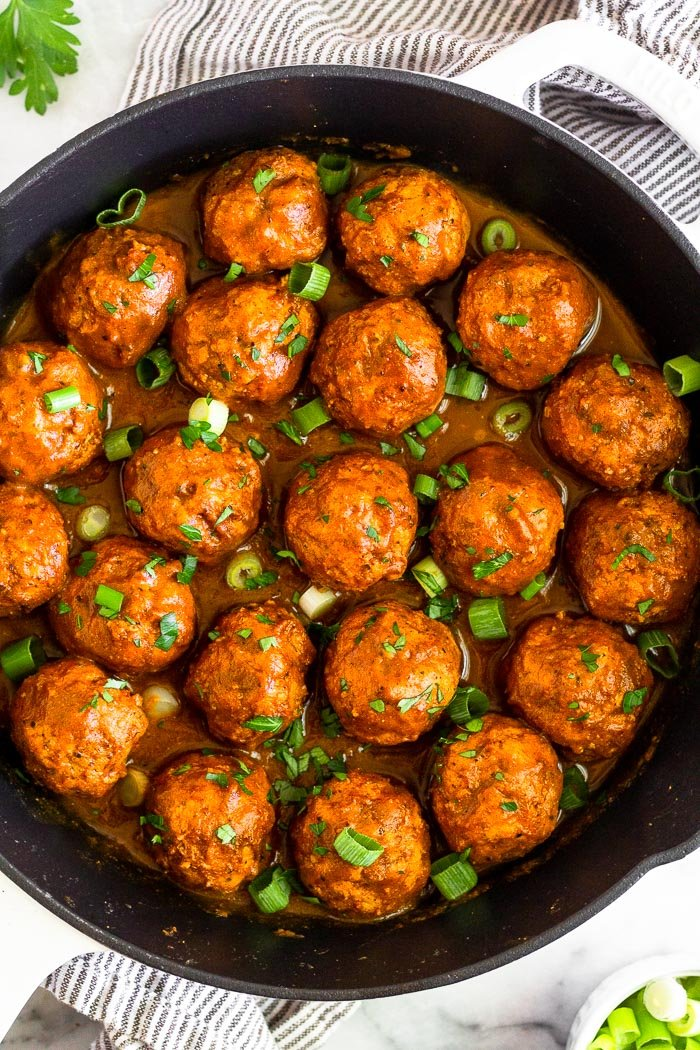 Overhead shot of BBQ chicken meatballs made in the instant pot. They are in a large cast iron with bbq sauce. chopped green onions, and chopped parsley. The pan is sitting on a towel with parsley and a bowl of green onions around it.