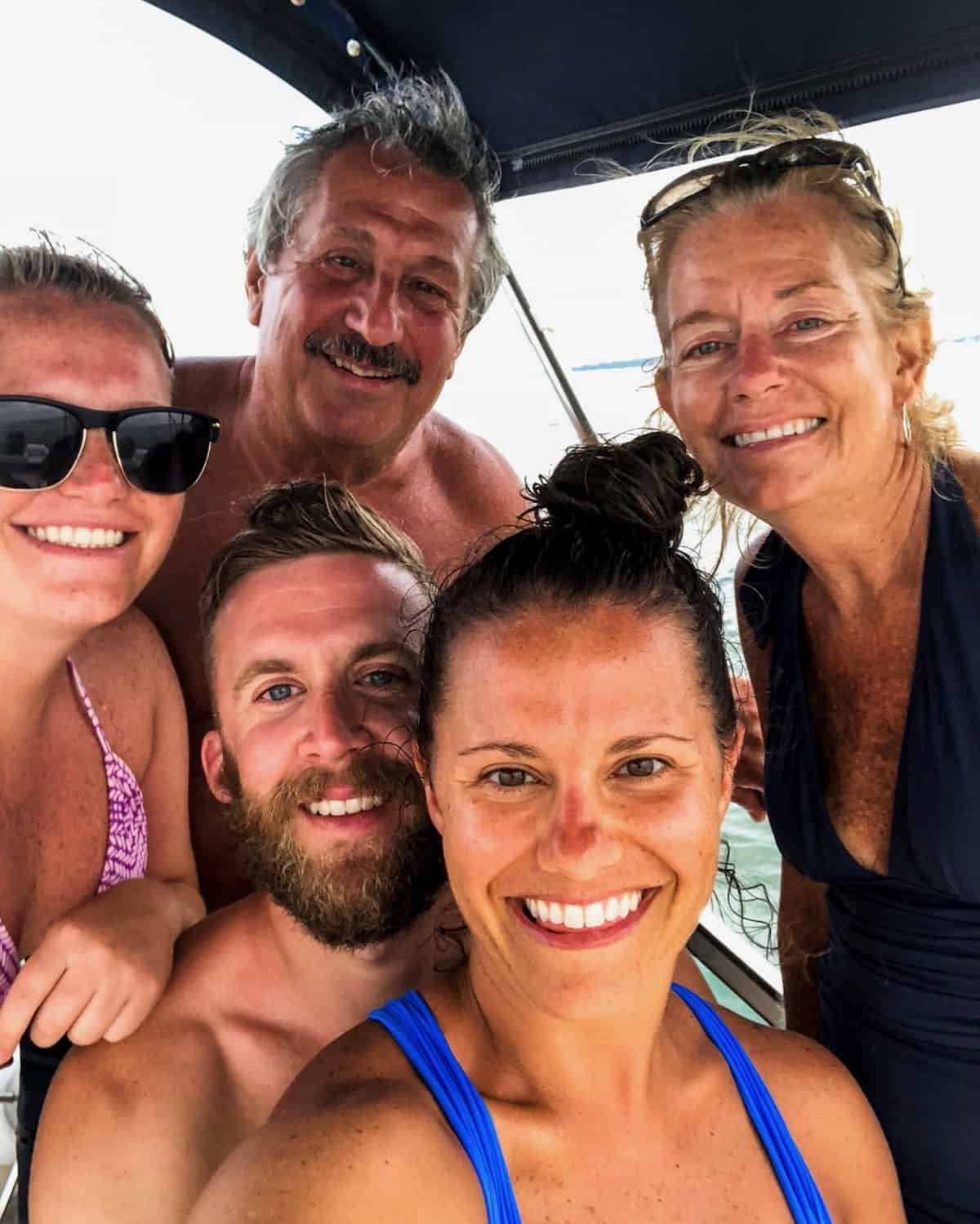 A family on a boat - a dad, mom, 2 sisters, and one of the sister's fiancé