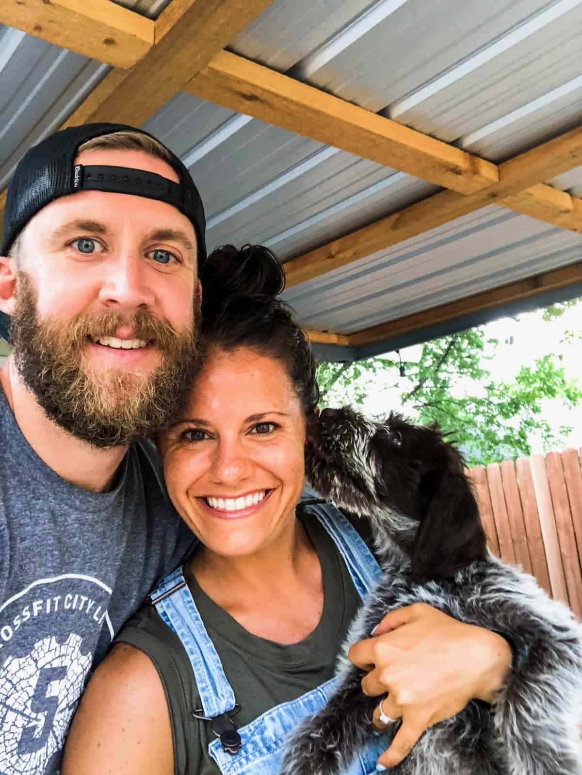 A girl, her fiancé, and their new puppy, who is licking her face, in a family photo outside