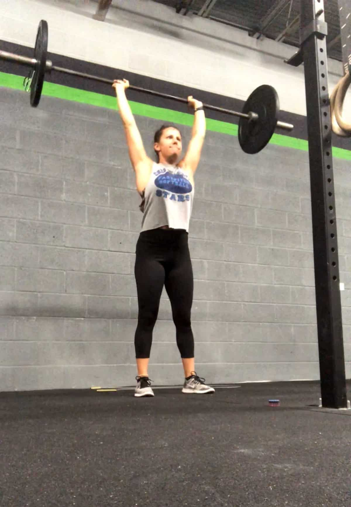 Girl in a CrossFit gym doing a push press with the barbell over her head