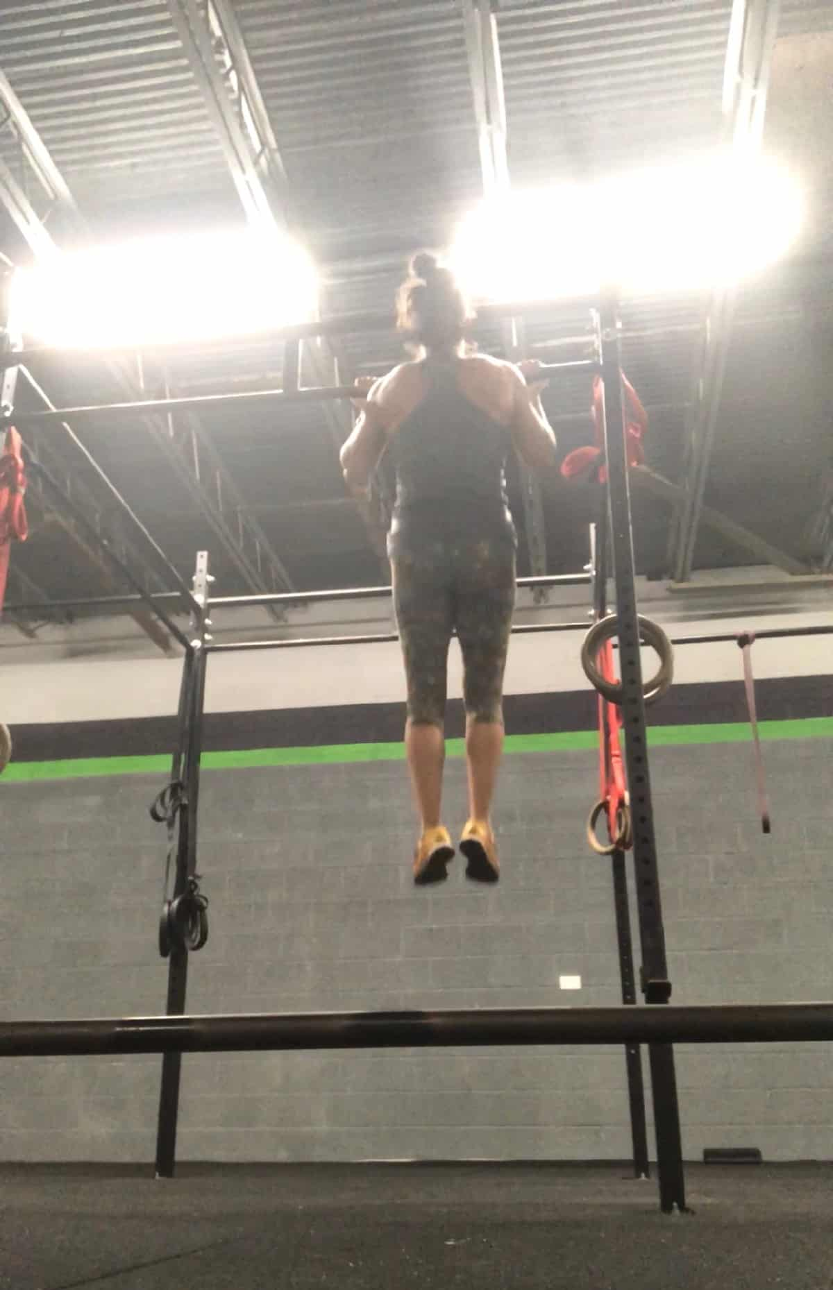 Girl with her chin over the bar doing a strict chin up