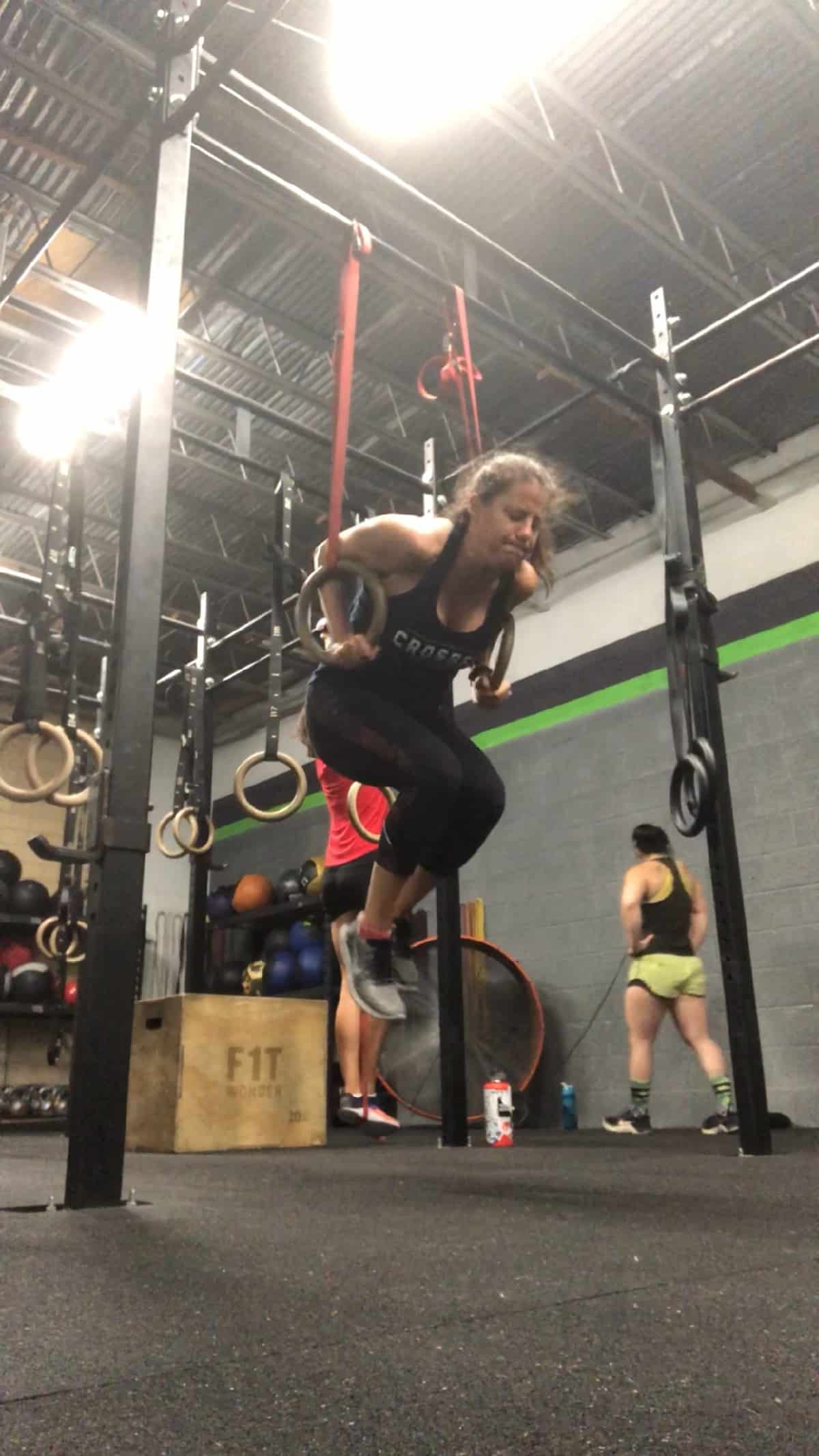 Girl in a CrossFit gym doing a ring dip