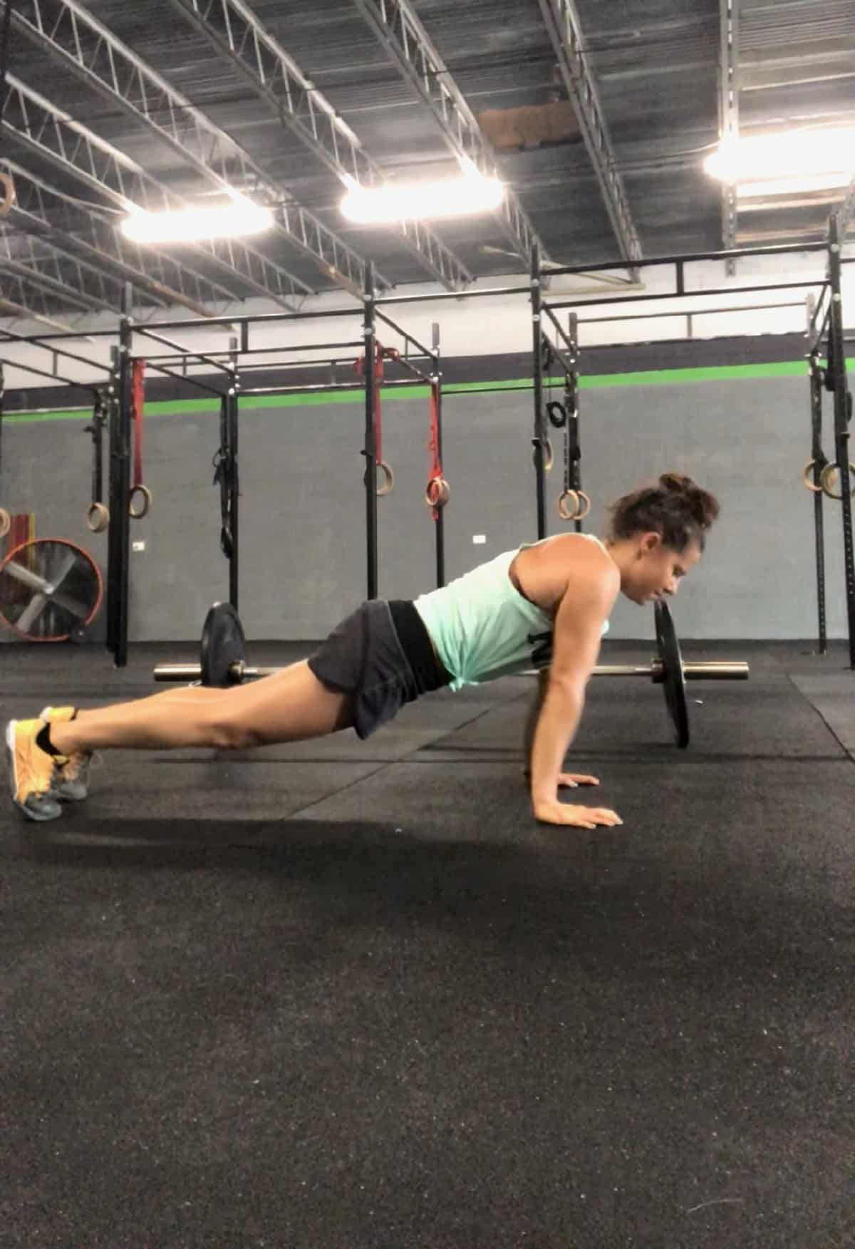 Girl on your feet and hands in a high plank position doing a push-up