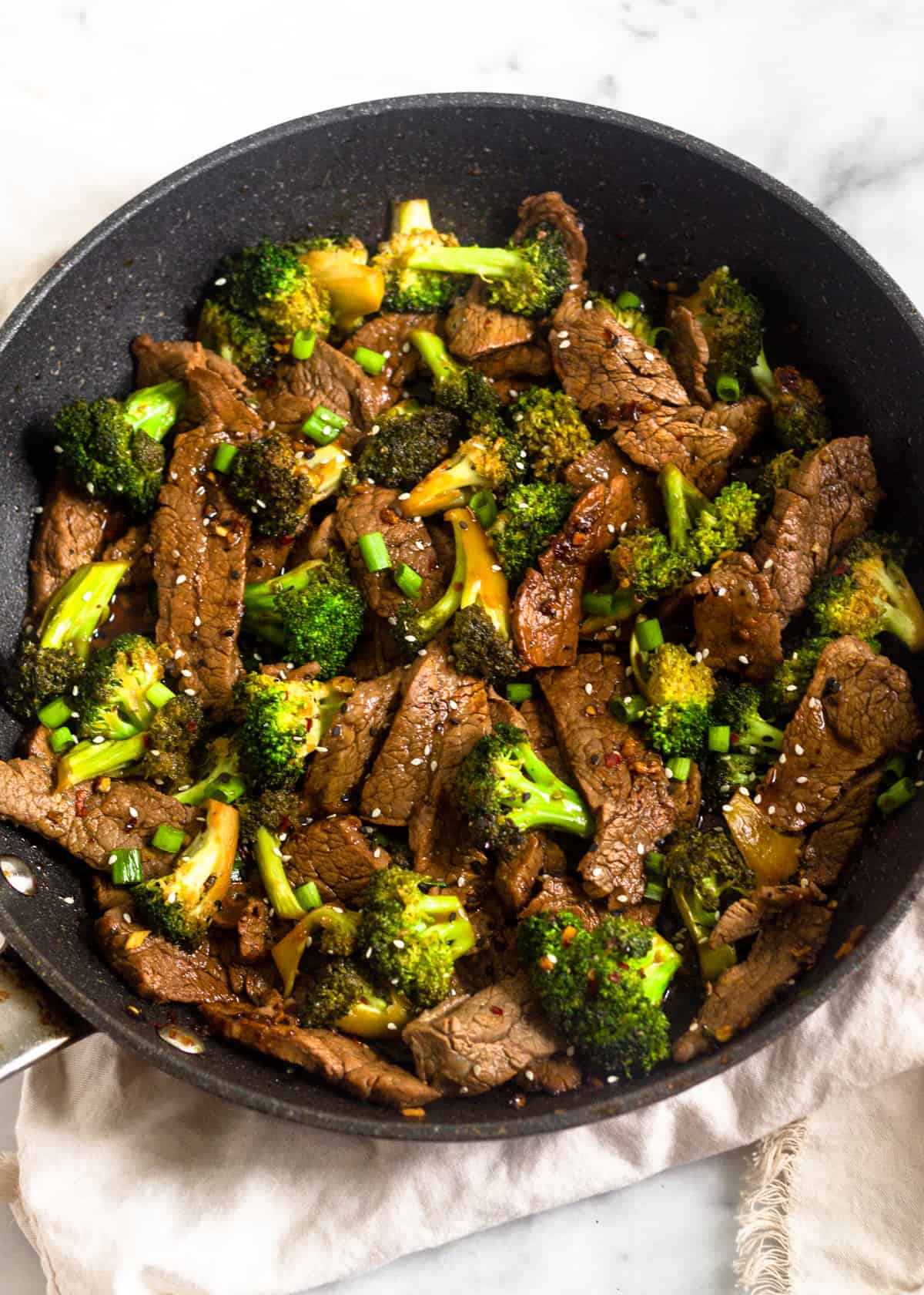 Large saute pan filled with whole30 and paleo beef & broccoli stir fry sitting on a white linen