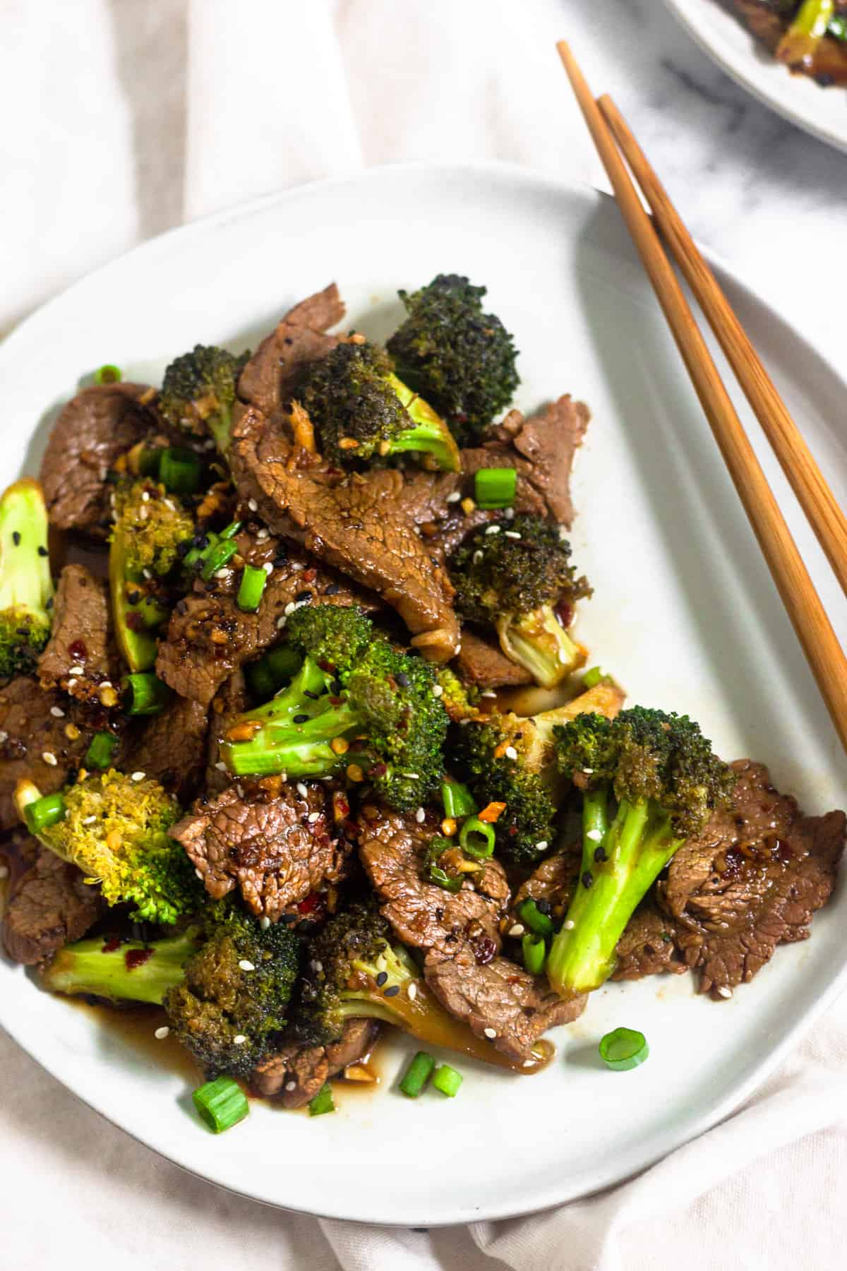 Large plate filled with healthy paleo beef & broccoli with wooden chop sticks sitting on the side of it
