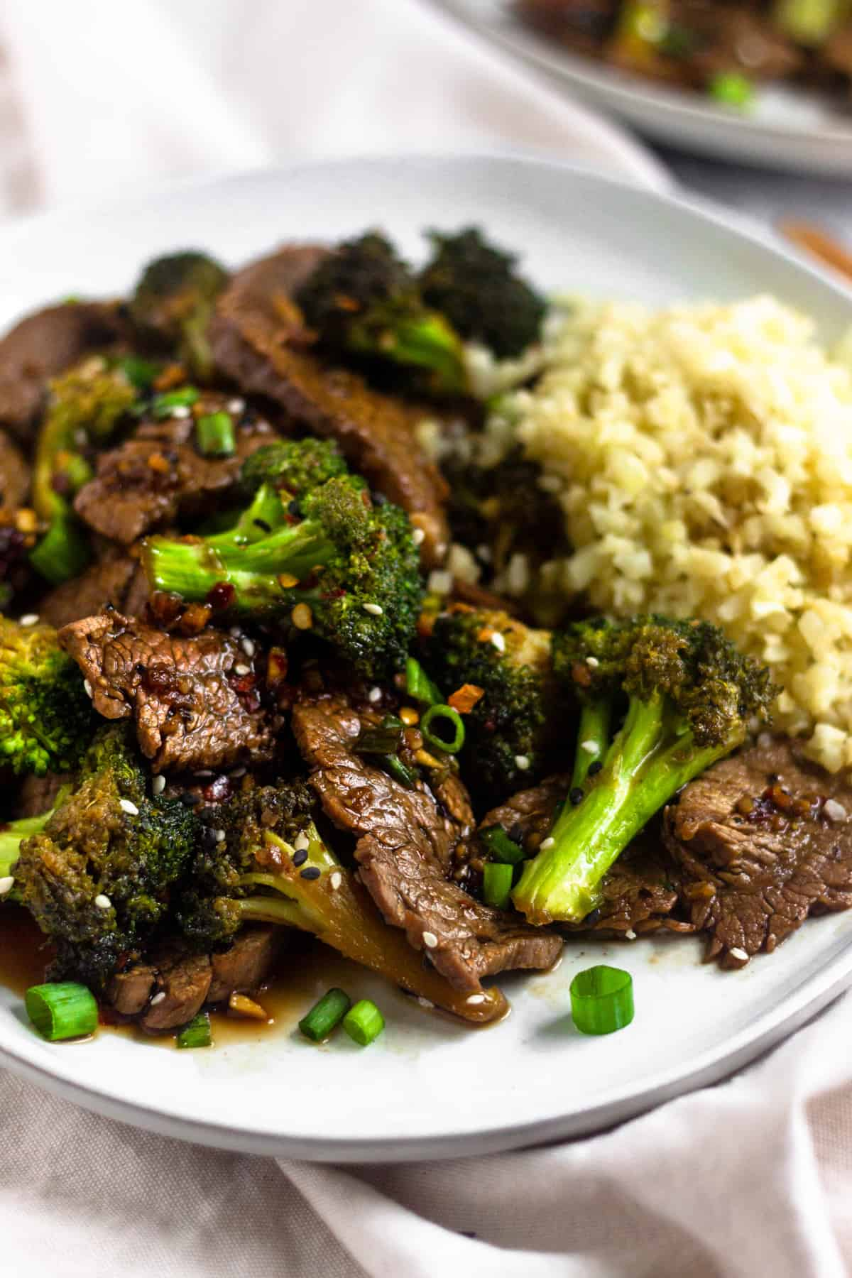 Close up of a plate of paleo beef & broccoli on a white plate on top of a white linen