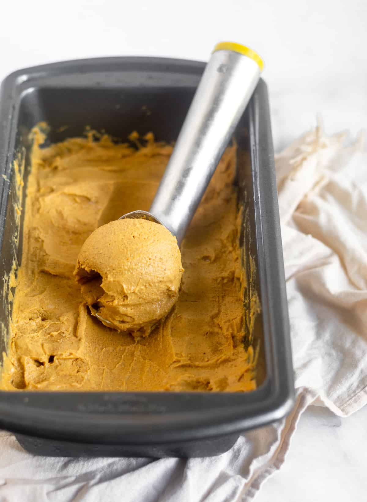 Small bread pan filled with dairy free and paleo pumpkin pie ice cream with a scoop of ice cream in an ice cream scooper in it.